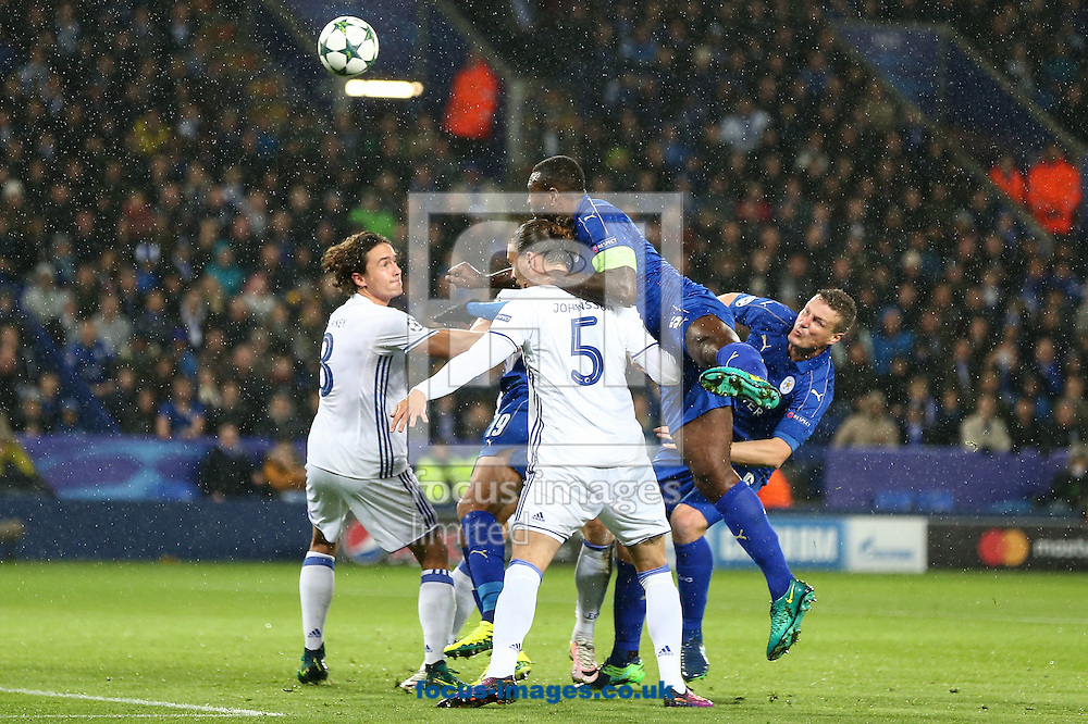 Wes Morgan of Leicester City (centre) competing in the air during the UEFA Champions League match at the King Power Stadium, Leicester<br /> Picture by Andy Kearns/Focus Images Ltd 0781 864 4264<br /> 18/10/2016