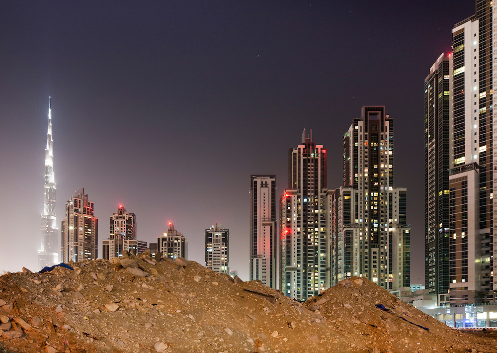 United Arab Emirates, Dubai, Debris pile and Burj Khalifa and construction site of new office towers and apartment blocks in Business Bay district at night