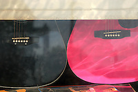 A black and pink guitar in a music shop window.