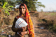 Bacchi Saran, a tribal wood gatherer from Kihuniya village holds up her family's copy of this week's newspapers as Shanti Adivasi, 52 (unseen), distributes newspapers in Manikpur, Chitrakoot, Uttar Pradesh, India on 4th December 2012. Shanti used to be a wood gatherer, working with her parents since she was 3, and later carrying up to 100 kg of wood walking 12km from the dry jungle hills to her home to repack the wood which sold for 3 rupees per kg. After learning to read and write in an 8 month welfare course, at age 32, she became a reporter, joining Khabar Lahariya newspaper since its establishment in 2002, and making about 9000 rupees per month, supporting her family of 14 as the sole breadwinner. Photo by Suzanne Lee for Marie Claire France.