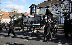 **NOTE: People in police uniform are not real policemen** © Licensed to London News Pictures. 09/12/2015. London, UK. Men dressed as a policemen walk alongside the carriage carrying the coffin as it travels to to funeral service. The funeral of former brothel keeper Cynthia Payne takes place at the South London Crematorium.  In 1980 Cynthia Payne was sentenced to 18 months for running a brothel at her house on Ambleside Avenue in Streatham. It was alleged, at the time, that judges and Members of Parliament were visitors to her establishment. Photo credit: Peter Macdiarmid/LNP