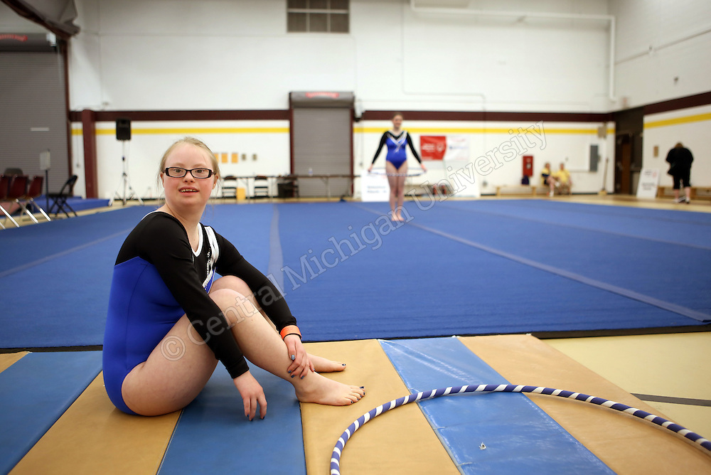 A gymnast poses for a portrait while another gymnast practices her routine during the 2015 Michigan Summer Special Olympics photo by Claire Abendroth