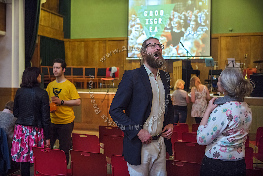 Sanderson Jones (centre) is talking to a woman attending The Sunday Assembly (today held inside Conway Hall in central London), an atheist service founded by British comedians Sanderson Jones and Pippa Evans in 2013, in London, England. The gathering is designed to bring together non-religious people who want a similar communal experience to a religious church. Satellite assemblies have been established in over 30 cities including New York, San Diego, and Dublin.