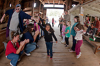 Ben Cartier and Kendora Harper enjoy square dancing to the music of Jacqueline and Dudley Laufman in the barn at Prescott Farm Environmental Education Center during Saturday's 2nd annual Harvest Festival.  (Karen Bobotas/for the Laconia Daily Sun)