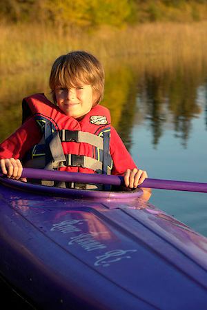 Young man kayaking in Katherine Lake, Riding Mountain National Park Manitoba.