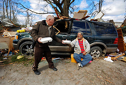 24 February 2016. Water tower Street, Convent, Louisiana.<br /> Devastation following a deadly EF2 tornado touchdown. 2 confirmed dead. <br /> Clarence Walters (center) sits beside the remains of his business partners destroyed trailer home and car. His friend was in the home when it was flipped over into the middle of the street. A local sheriff hands out food.<br /> Photo©; Charlie Varley/varleypix.com