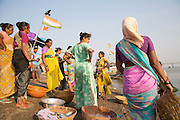 Indian women wait on the beach for the catch to return to shore. Whilst the men work on the boat it is the women's job to collect and prepare the fish for market.