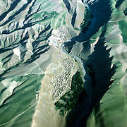 3 June 1976<br /> Between Kishm and Faizabad. Settlement on very bare slope. Trees below. Ranges covered by grasses.