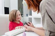 Woman applying nail polish on little girl's hand