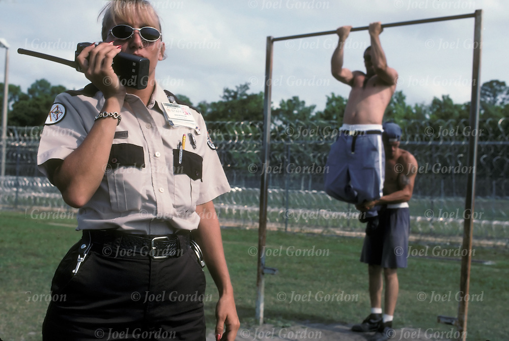 Putnam Correctional Institution, Minimum Security Prison, Caucasian female correction officer talking on radio as inmates in background use exercise bars during recreation time
