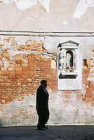Silhouette of senior man walking past brick building Venice Italy