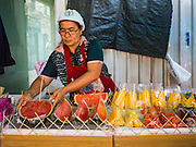 26 FEBRUARY 2016 - BANGKOK, THAILAND: A woman sells fruit in front of the fence blocking access to the demolition site in the Verng Nakorn Kasem neighborhood. Verng Nakorn Kasem, also known as the Thieves' Market, was one of Bangkok's most famous shopping districts. It is located on the north edge of Bangkok's Chinatown district, it grew into Bangkok's district for buying and selling musical instruments. The family that owned the land recently sold it and the new owners want to redevelop the famous area and turn it into a shopping mall. The new owners have started evicting existing lease holders and many of the shops have closed. The remaining shops expect to be evicted by the end of 2016.      PHOTO BY JACK KURTZ