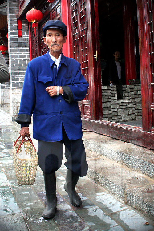 Wearing a blue shirt and a Mao's style flat cap, an old chinese man walks in the street to reach the market. He carries an empty basket and wellington boots.