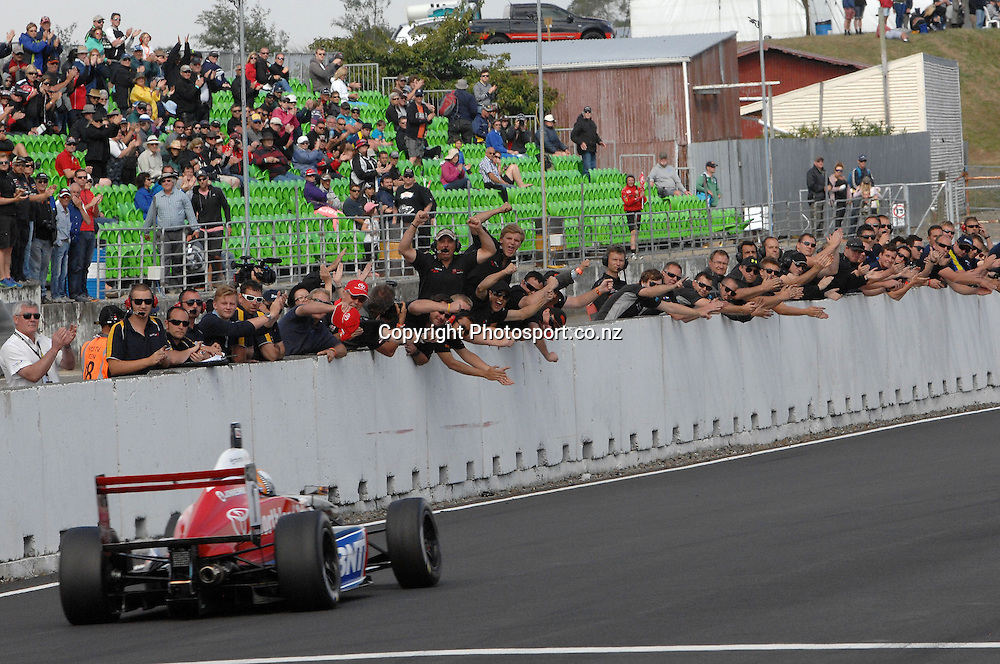 Nick Cassidy from Auckland in his Toyota FT40, crosses the finishing line for New Zealand Grand Prix, which he has now won for the third consecutive year, and is congratulated by all the teams.