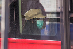 © Licensed to London News Pictures. 01/03/2020. London, UK. A woman wearing a surgical face mask travels on a bus, as a precaution against new type coronavirus (COVID-19). Twelve more people have tested positive for coronavirus in the UK, bringing the total number of cases to 35. Photo credit: Dinendra Haria/LNP