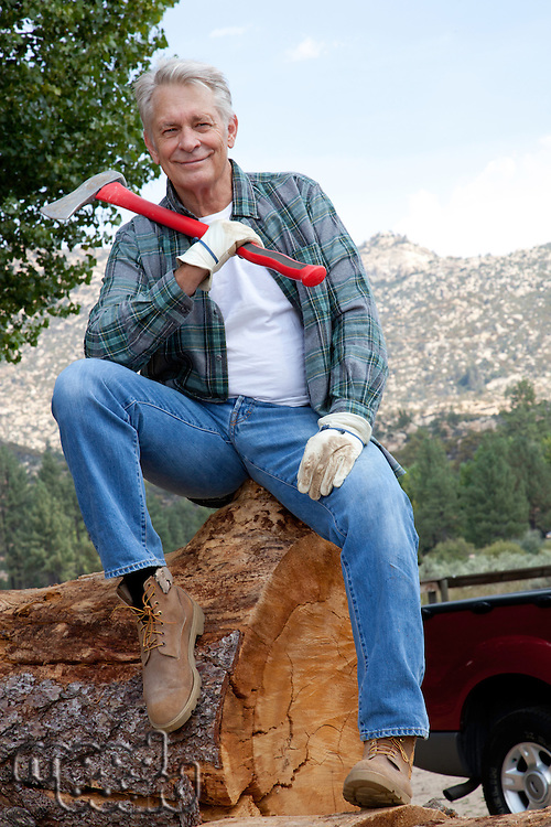 Lumberjack sitting on huge tree trunk with an axe