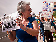 18 APRIL 2011 - PHOENIX, AZ: HIEDY SCHMIDT pickets the office of Sen. John McCain Monday. About 50 members of MoveOn.org gathered at the office of US Sen. John McCain (R-AZ) in Phoenix, AZ, Monday, Apr. 18, to draw attention to corporations that don't pay U.S. taxes. A representative of the group went into McCain's office present the Senator's staff with a tax bill for the 12 corporations they say paid no US income taxes.      Photo by Jack Kurtz