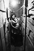 Jovem mãe e seu filho morando nas construções de um CIEP abandonado na favela Rubens Vaz no Complexo da Maré, Rio de Janeiro..Young mother and his/her son living in the constructions of an abandoned CIEP in the slum Rubens Vaz in the Compound of the Tide, Rio de Janeiro.