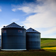A photographer is hidden among the grain sylos of a farm in the Palouse of Washington State.