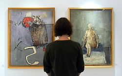 """© Licensed to London News Pictures. 15/11/2012. London, UK A woman looks at two David Hockney Paintings from his time at the College. (L """"Composition - Thrust"""" and R """"Nude-Seated"""" both completed in 1962 Hockney was a Painting student 1959-62)  The Royal College of Art is celebrating its 175thanniversary with a major exhibition featuring more than 350 works of art and design by over 180 RCA graduates and staff, including Henry Moore, Barbara Hepworth, Tracey Emin, David Hockney, Peter Blake, Bridget Riley and Lucian Freud. The RCA is the world's oldest art and design university in continuous operation. Its first students comprised a small group of teenage boys; today it educates some 1,200 postgraduate students from 55 different countries.. Photo credit : Stephen Simpson/LNP"""
