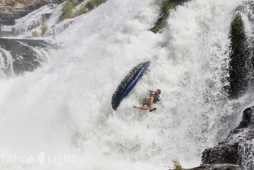 Kevin Vilkin throws his paddle as he bails out of his inflatable kayak as it goes over the pit falls during a pit river release august 19, 2007. Model release available..
