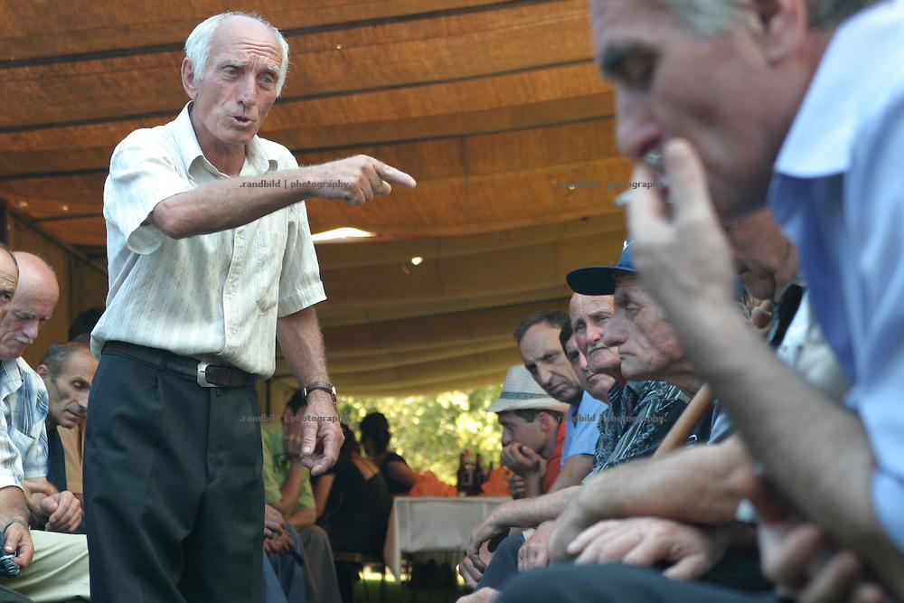 Georgien/Abchasien, Gudauta, 2006-08-26, Auf dem traditionellen Treffen des Hagba-Clans in Abchasien kommen 125 Familien zusammen. Vor dem Fest diskutieren die Männer die Probleme und sammeln Geld für notleidende Familienmitglieder. Abchasien erklärte sich 1992 unabhängig von Georgien. Nach einem einjährigen blutigen Krieg zwischen den Abchasen und Georgiern besteht seit 1994 ein brüchiger Waffenstillstand, der von einer UNO-Beobachtermission unter personeller Beteiligung Deutschlands überwacht wird. Trotzdem gibt es, vor allem im Kodorital immer wieder bewaffnete Auseinandersetzungen zwischen den Armee der Länder sowie irregulären Kämpfern.  (A meeting of the Hagba clan in Abkhazia. 125 families depends on that clan. At the traditional meeting every summer the men discuss the problems and collecting money for needy family members. After that the party begins. Abkhazia declared itself independent from Georgia in 1992. After a bloody civil war a UNO mission observing the ceasefire line between Georgia and Abkhazia since 1994. Nevertheless nearly every day armed incidents take place in the Kodori gorge between the both armys and unregular fighters )