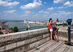 Couple taking a selfie from terrace on Buda Hill with Pest, the famous Hungarian Parliament building, and the Danube River in the background.