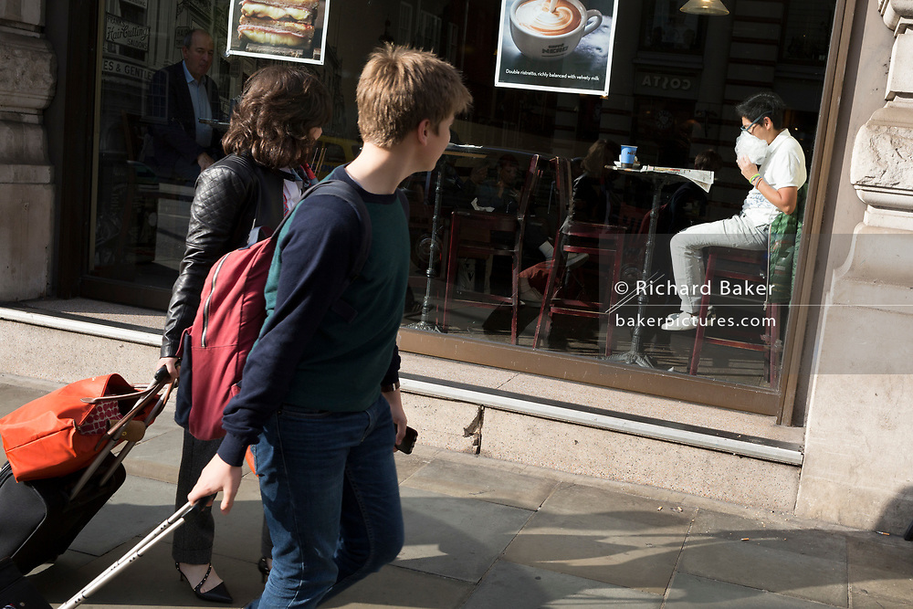 Passers-by look at a man eating his own food from a plastic bag in the sunlit window of a central London cafe, on 25th October 2018, in Piccadilly, London, England.