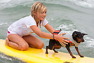 Bella Pringle holds onto her dog Chiquita while catching a wave.