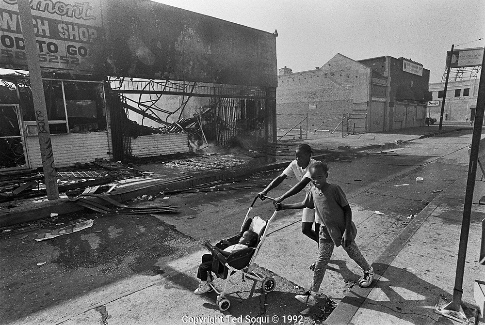 A woman pushing a stroller with her daughter on S. Vermont Ave and 86th Street in South Central Los Angeles. <br /> <br /> 25 before and after LA92 photo project.