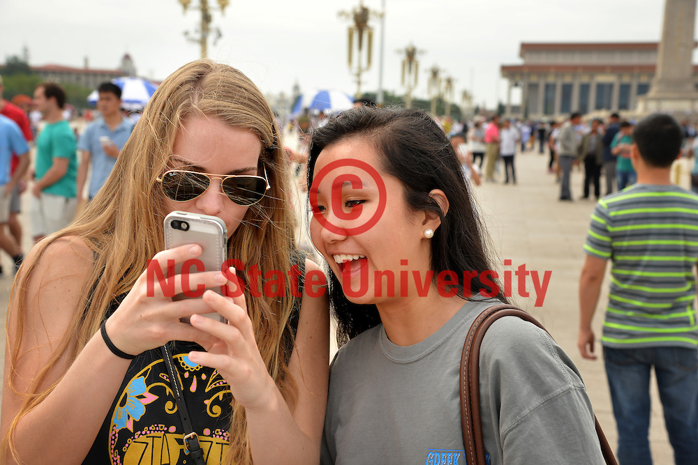 Poole College of Management Study Abroad students Gina Black and Angela Wang check photos they've taken at Tiananmen Square.