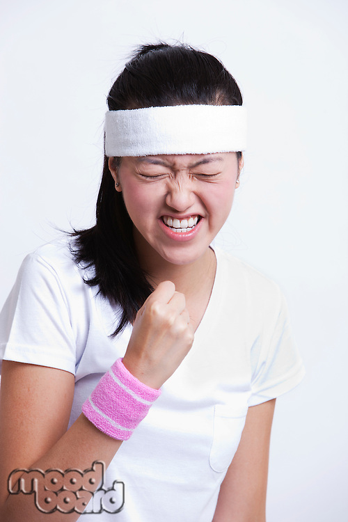 Young female tennis player celebrating success against white background