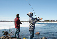 Matthew Cote casts his line from the shore of Lake Opechee at the Lakeport Dam with David Manita on opening day of landlocked fishing season.   (Karen Bobotas/for the Laconia Daily Sun)