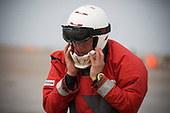 One of the competitors putting on his crash helmet before one of the races at the European Kite Buggy Championships at Hoylake, Wirral, north west England. Around 75 buggies, with both male and female pilots, from 10 countries took part in the annual event which lasted from 5-9 September 2011. The three-wheeled, single-seated, steel frame buggy was powered  by a traction, or power kite and could achieve speeds of up to 70mph/110km/h.