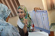 An officer explain how to vote to a Libyan Woman during the first democratic election after 42 years of dictatorship.