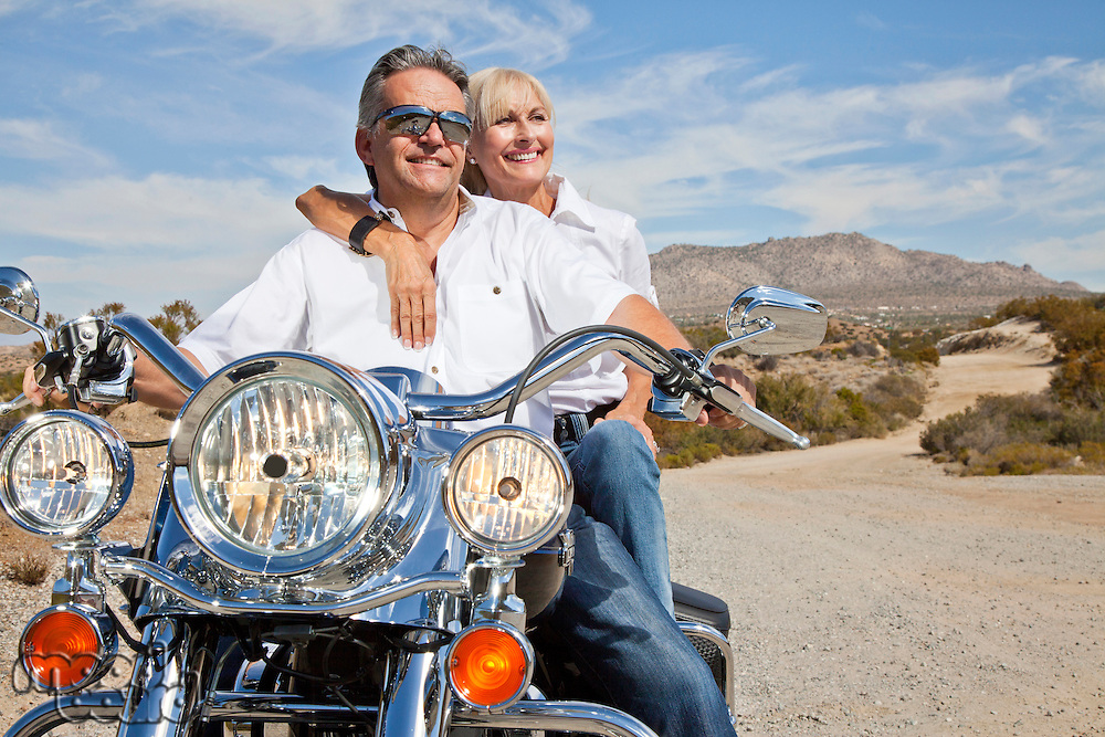 Senior couple on desert road sitting on motorcycle
