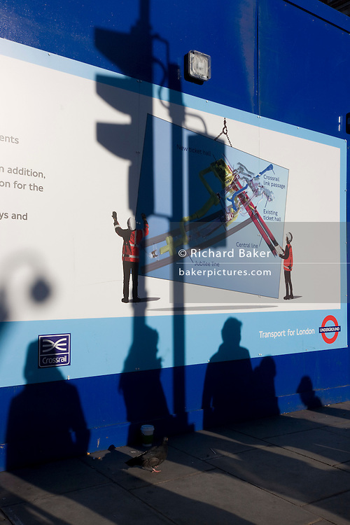Anonymous peoples' shadows and a London Crossrail construction site hoarding.