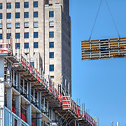 New hotel construction by Chartwell Hospitality in downtown Kansas City, with art deco Power and Light Building, also undergoing renovation in background.