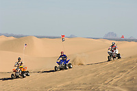 Three Young Men Riding ATVs on Dunes