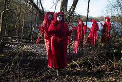 Harefield, UK. 18 January, 2020. The Red Rebel Brigade arrives to join activists from Extinction Rebellion, Stop HS2 and Save the Colne Valley as they reoccupy the Colne Valley wildlife protection camp from which all but two activists had been evicted by bailiffs the previous week on the second day of a three-day 'Stand for the Trees' protest in the Colne Valley timed to coincide with tree felling work by HS2. 108 ancient woodlands are set to be destroyed by the high-speed rail link.
