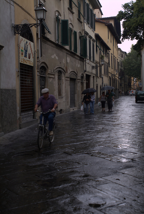 Man on bicycle and pedestrians in the rain on street in Lucca, Italy