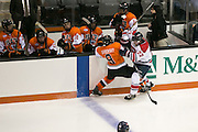 RIT Senior Captain Matt Garbowsky absorbs a hit from Brock University's Tyler Anton in front of the Tigers bench during a game at the Gene Polisseni Center on Saturday, October 4, 2014.
