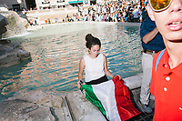 """ROME, ITALY - 20 JUNE 2017: A Spanish student with an Italian flag sits by the Trevi Fountain, though it is forbidden, in Rome, Italy, on June 20th 2017.<br /> <br /> The warm weather has brought a menacing whiff of tourists behaving badly in Rome. On April 12, a man went skinny-dipping in the Trevi fountain resulting in a viral web video and a 500 euro fine.<br /> <br /> Virginia Raggi, the mayor of Rome and a national figurehead of the anti-establishment Five Star Movement,  issued an ordinance involving harsher fines for eating, drinking or sitting on the fountains, for washing animals or clothes in the fountain water or for throwing anything other than coins into the water of the Trevi Fountain, Bernini's Four Fountains and 35 other city fountains of artistic or historic significance around the city.  """"It is unacceptable that someone use them to go swimming or clean themselves, it's an historic patrimony that we must safeguard,"""" Ms. Raggi said."""
