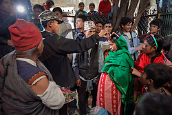Durga, 16, applies sindoor, or vermillion powder, to his young bride Niruta's part during their wedding ceremony in Kagati village Nepal on Jan. 23, 2007, which was the auspicious day of Vasant Panchami, a Hindu holiday celebrating the coming of spring. Niruta, 14, was nine-months pregnant during the ceremony, attended by friends and relatives. Durga's father hadn't liked the idea of his son abandoning his education and marrying young, but after Durga's mother's death, the family desperately needed help in both the home and the fields. So they found a suitable young bride.<br />