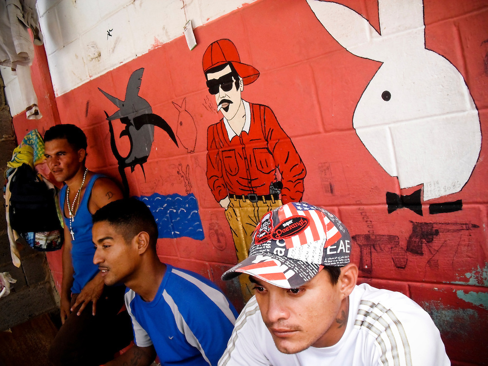 "Josmary Ramirez, 24, (right) sits in his living quarters in San Antonio prison in Porlamar, Venezuela under paintings of a Playboy bunny and Ismael, a ""santo malandro"" (gangster saint) for followers of Maria Lionza, the fertility goddess of a popular Venezuelan belief system known as espiritismo. Believers pray to Ismael, a deceased gangster, for protection in the streets. His image, along with the Playboy bunny, is plastered around the prison, and many prisoners have tattoos of his image as well."