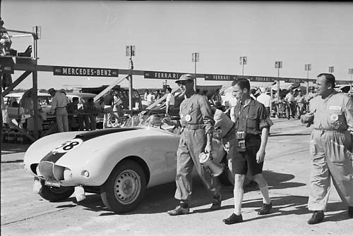 """Stan """"Wacky"""" Arnolt, automaker and driver, stands at right ready to race his Arnolt Bristol no. 58 at Sebring 1955 (ID confirmed by """"Wacky"""" on left breast of his driver's suit)"""