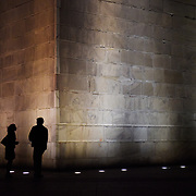 Two people are silhouetted against the lights that line the base of the Washington Monument in Washington, D.C.