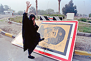 A Kuwaiti woman wearing a full body chadri kicks a portrait of Saddam Hussein during celebrations following the liberation of Kuwait from Iraqi occupation by coalition forces February 28, 1990 in Kuwait City, Kuwait.