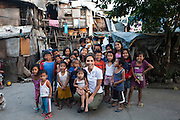 Myleene Klass, a high profile UK celebrity, TV host, violinist and pianist, poses for a portrait with children in an urban slum where she had visited an under-privileged mother and her family in Paranaque, Metro Manila, The Philippines on 19 January 2013. Photo by Suzanne Lee for Save the Children UK