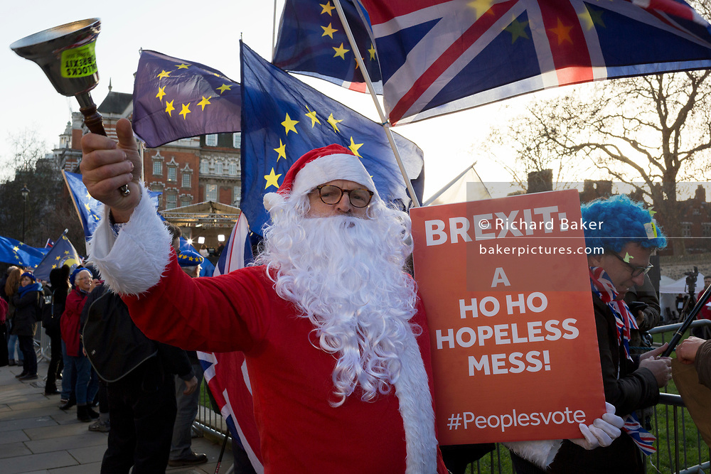 As Prime Minister Theresa May tours European capitals hoping to persuade foreign leaders to accept a new Brexit deal (following her cancellation of a Parliamentary vote), a pro-EU Santa rings a Brexit bell during a protest opposite the Houses of Parliament, on 11th December 2018, in London, England.